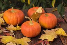 Four Ripe Pumpkins With Autumn Leaves On A Wooden Table.
