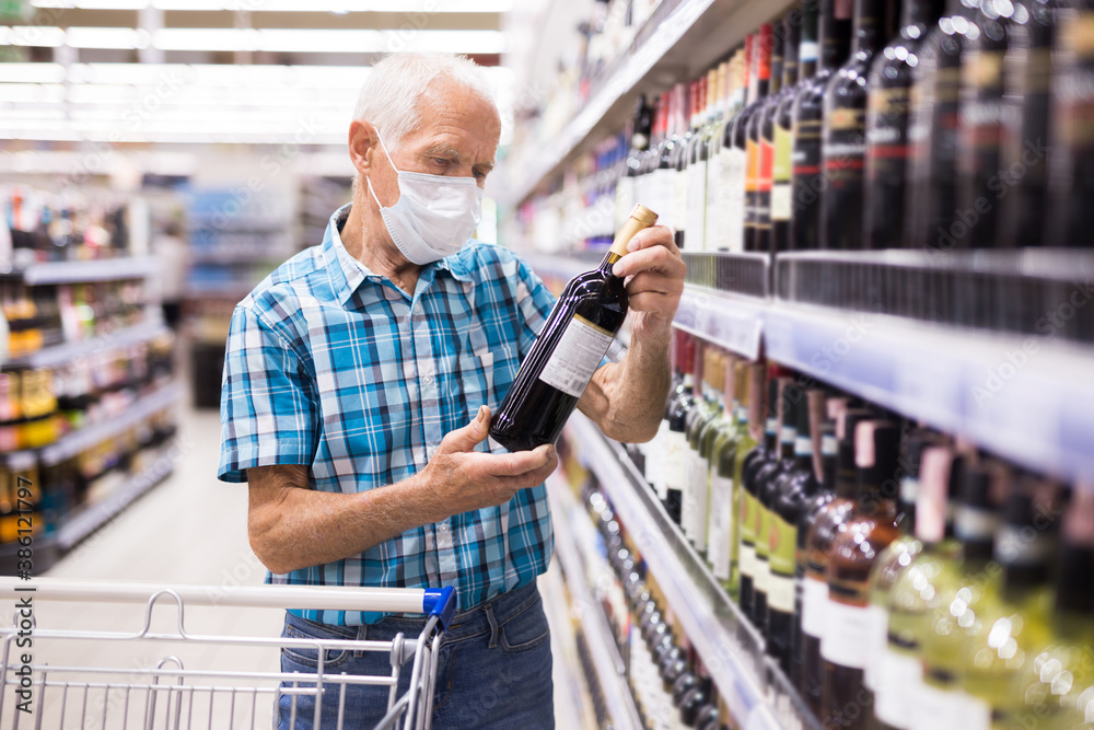 Fototapeta mature european man wearing mask with covid protection chooses bottle of alcohol in supermarket