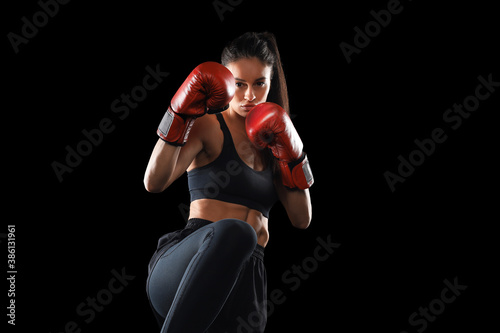 Obraz Kickboxing woman in activewear and red kickboxing gloves on black background performing a martial arts kick. Sport exercise, fitness workout. - fototapety do salonu