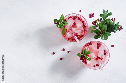 Pink cold berry cocktail with lingonberry, ice and green leaves in sunbeam on white wooden table, copy space, top view.