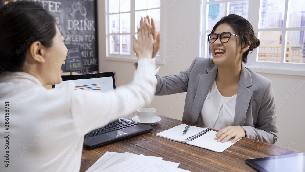 Fototapeta Excited teammates gesturing yes sign. coworkers laughing celebrating shared goal achievement on laptop computer meeting in coffee shop. colleagues happy for business success and giving high five