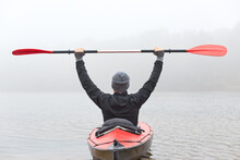 Back View Of Man Rowing Kayak Across River Water In Foggy Morning, Raising His Paddle Up, Wearing Black Jacket And Gray Cap, Looks In Front Of Him.