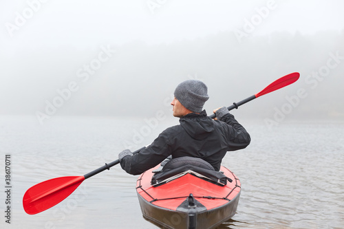 Fotomural Back view of young handsome man kayaking in river, spends foggy morning in canoe, extreme sport, man in black jacket and gray cap rowing boat and looking aside