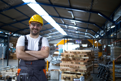Obraz Portrait of factory worker with arms crossed standing by industrial machine. - fototapety do salonu