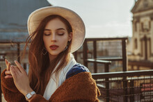 Outdoor Fashion Portrait Of Young Elegant Fashionable Brunette Woman, Model Wearing Stylish White Hat, Wrist Watch, Scarf, Posing At Sunset, In European City. Copy Empty Space For Text