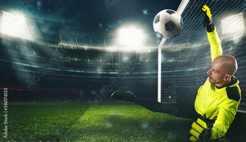 Photo Soccer goalkeeper, in fluorescent uniform, that makes a great save and avoids a