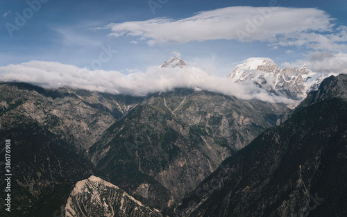 Fotomural Snow peaked Himalayas shrouded in clouds and mountain slopes