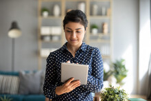 Millennial Indian Ethnicity Business Woman Standing In Cozy Room Working Remotely Using Tablet Portable Device Text Message Contact Distantly With Client. Make E-shopping Buy On E-commerce Web Concept