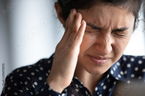 Closeup view frown face of indian woman feeling strong headache touch temple to Wallpaper Mural