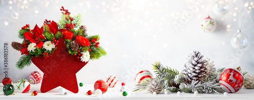 Festive winter flower arrangement in vase of red star shape and Christmas baubles on table. Christmas flower composition for holiday.
