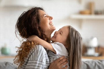 Close up side view overjoyed smiling young mother and daughter hugging and laughing, enjoying tender moment, happy mum and adorable preschool girl kid cuddling, having fun together at home