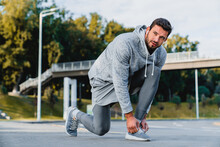Full Length Portrait Of A Fit Young Male Athlete Tying Shoelaces Before Jogging Near The City Bridge