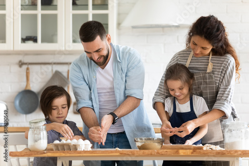 Happy mother and father with two kids baking together, standing at wooden counte Canvas Print