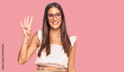 Fotomural Young hispanic woman wearing casual clothes and glasses showing and pointing up with fingers number four while smiling confident and happy