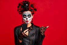 Girl With Sugar Skull Makeup With A Wreath Of Flowers On Her Head And Skull, Wearth Lace Gloves And Leather Jacket, Shocked With News From Her Phone Isolated On Red Background