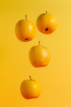 Four Ripe Juicy Apples Falling Or Levitating On Simple Yellow Background Showing Healthy Lifestyle And Vegetarian.