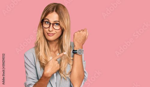 Beautiful blonde young woman wearing business clothes in hurry pointing to watch time, impatience, looking at the camera with relaxed expression - 386214352