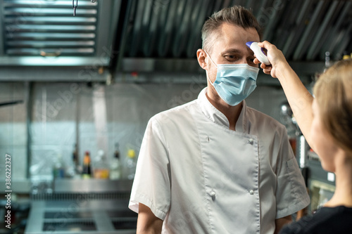 Fotografia Contemporary chef in white uniform and protective mask looking at young woman