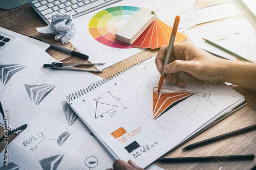 Photo Graphic designer drawing sketches logo design.