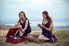Two Hippie Woman Are Lying In A Field On A Mountain