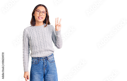 Fotografie, Tablou Young beautiful chinese girl wearing casual clothes showing and pointing up with fingers number three while smiling confident and happy