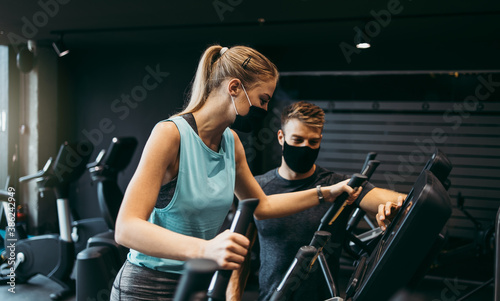 Obraz Young fit and attractive woman at body workout in modern gym together with her personal fitness instructor or coach. They wearing protective face masks. Coronavirus world pandemic and sport theme. - fototapety do salonu