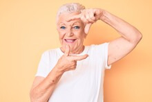 Senior Beautiful Woman With Blue Eyes And Grey Hair Wearing Classic White Tshirt Over Yellow Background Smiling Making Frame With Hands And Fingers With Happy Face. Creativity And Photography Concept.