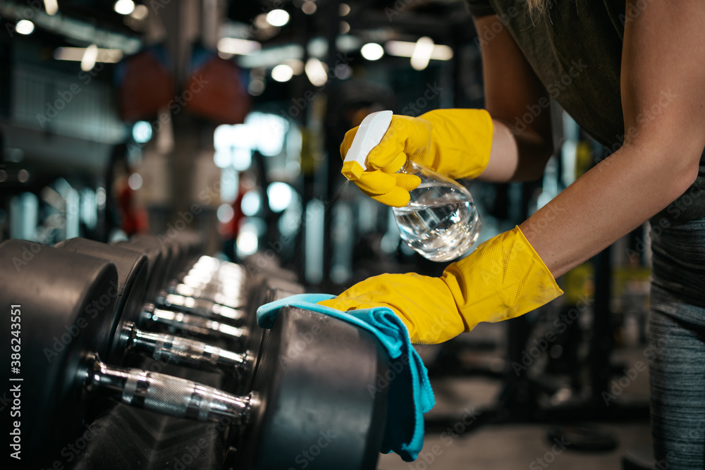 Fototapeta Young female worker disinfecting cleaning and weeping expensive fitness gym equipment with alcohol sprayer and cloth. Coronavirus global world pandemic and health protection safety measures.