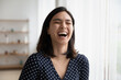 Close up of overjoyed young asian woman laugh at good funny joke indoors. Happy smiling millennial Vietnamese female have fun talking communicating, show optimism and happiness. Humor concept.
