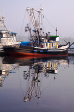 Colorful, Weathered Fishing Boat In A Marina On A Foggy Day