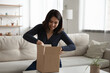 Excited millennial asian woman sit in living room open unpack cardboard box with internet order. Happy young Vietnamese female unbox package parcel shopping online from home. Good delivery concept.