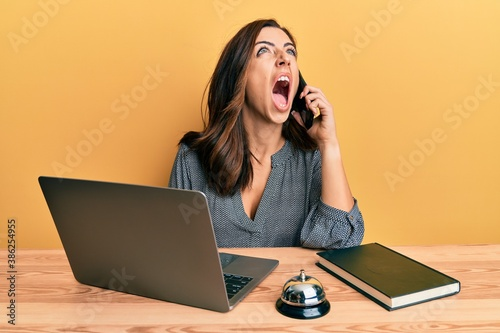Fotografering Young brunette woman working at hotel reception talking on the phone angry and mad screaming frustrated and furious, shouting with anger looking up