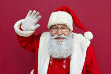 Happy Funny Senior Old Bearded Santa Claus Wearing Costume, Hat And Glasses Waving Hand Looking At Camera, Greeting On Merry Christmas Isolated On Red Background, Headshot Portrait.