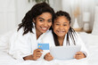 canvas print picture Black Mother And Daughter In Bathrobes Posing With Digital Tablet And Credit Card