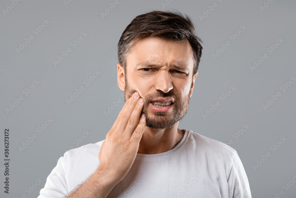 Fototapeta Man suffering from strong tooth pain, grey background