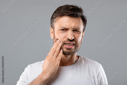 Obraz Man suffering from strong tooth pain, grey background - fototapety do salonu
