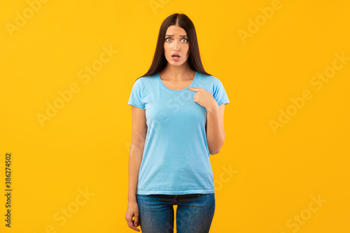 Fototapeta Portrait of woman pointing finger at herself