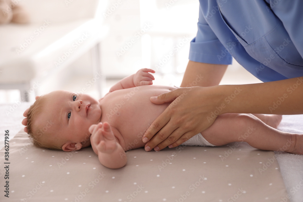 Fototapeta Doctor examining cute baby in clinic, closeup. Health care