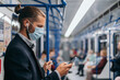 man in a protective mask standing in a subway car.