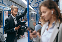 Young Man Reading A Book On A Subway Train.