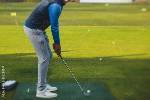 Group of golfers practicing and training golf swing on driving range practice, m Fototapet