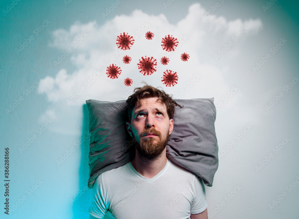 Fototapeta Coronavirus, covid-19 phobia, fear of pandemics. Man laying in bad and thinking about danger of a virus