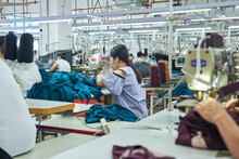 Employee's Working With Their Sewing Machines In Clothing Factory