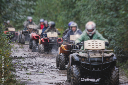 Fotografiet Group of riders riding atv vehicle on off road track, process of driving ATV veh