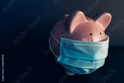 Global economy during coronavirus pandemic. Piggy bank wearing surgical face mask. Financial crisis, banking concept.