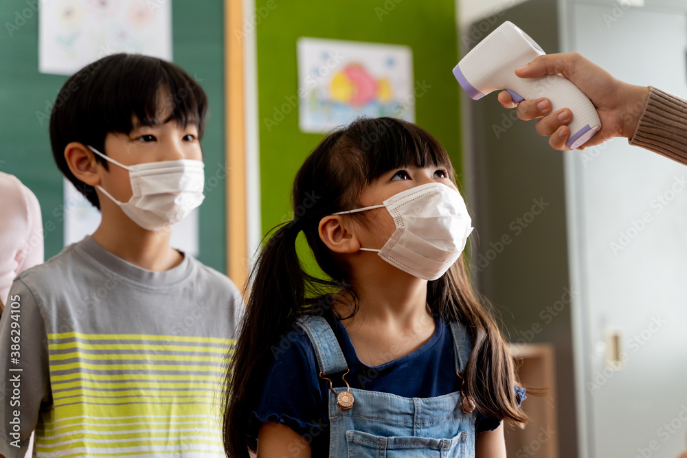 Fototapeta Group of Asian students in school building checked and scanned for temperature check. Elementary pupils are wearing a face mask and line up before entering into classroom. Covid-19 school reopen