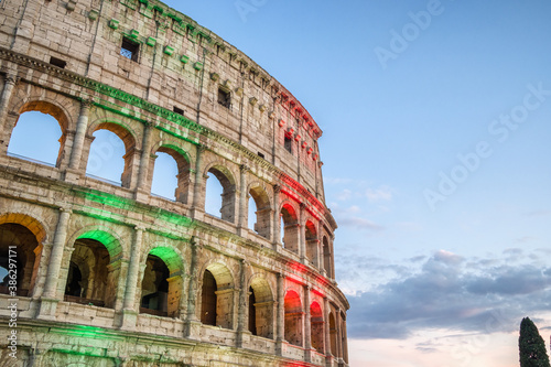 The famous Colosseum in Rome illuminated in Italian flag tricolore at twilight