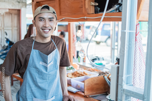 Asian male seller in apron smiles standing in front of the cart stall Fotobehang