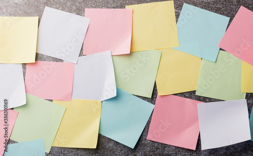 Obraz Many blank multicolored paper stick note list on concrete wall background, Business reminder memory post-it notes work today concept - fototapety do salonu
