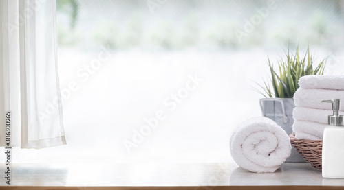 Fotografia Clean white bath towels  on wooden counter table, copy space.